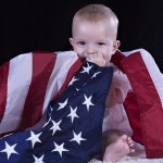 Baby sitting and wrapped by the American flag