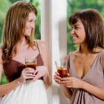 Two women standing together with glasses of ice tea